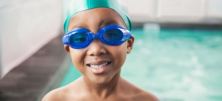 Cute little boy smiling at the pool at the leisure center