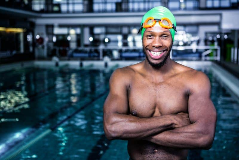 Fit NL Aquatic Center personal trainer and swimmer standing with arms crossed in swimming pool