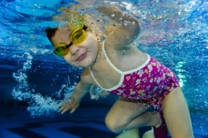 happy cute girl toddler swimming underwater